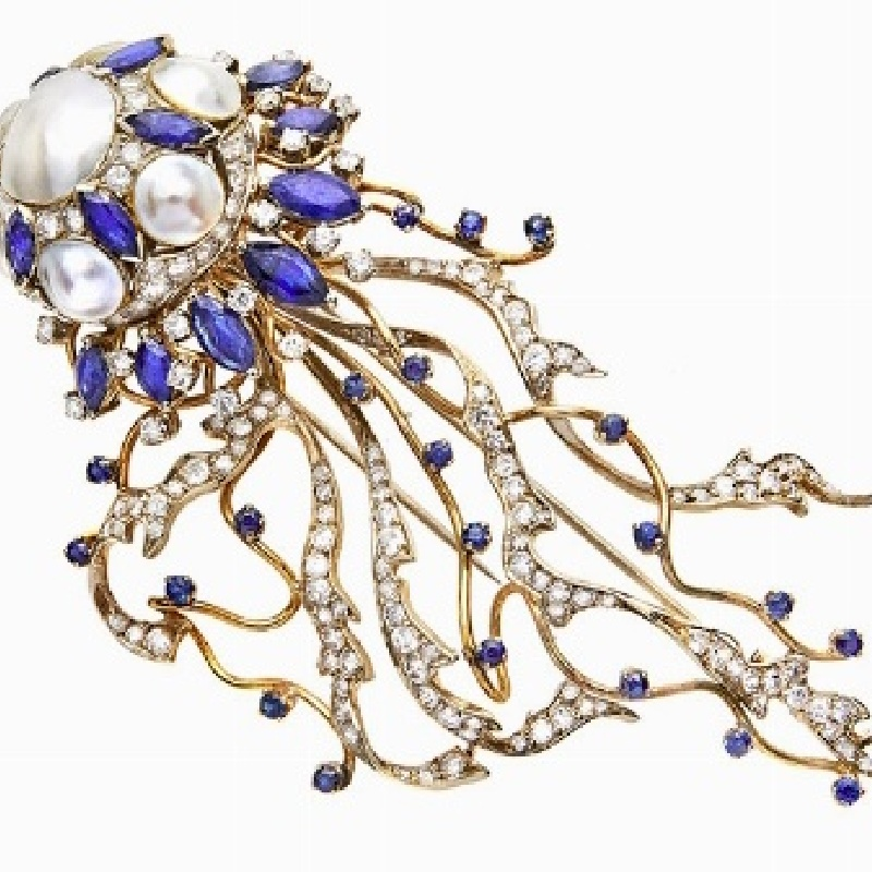 BROOCH, ENRICO SERAFINI, FLORENCE, SIXTIES  MATERIAL: yellow, white, diamonds, sapphires and pearls Mabe DESCRIPTION: brooch designed as a jellyfish, with Mabe pearl center, end with Mabe pearls alternating with oval cut sapphires, long tentacles embellished with diamonds and sapphires, signed Serafini, bears the mark 750 MEASURES : lung. 9.5 WEIGHT: sapphire 8 ct, diamonds ct 4.50, 33.5 g